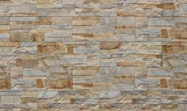 Stone wall cladding for exterior made of rock stripes panels . The colors are shades of light brown and gray.  royalty free stock photo