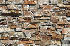 Stone wall cladding made of  brown and gray natural rocks. Background and texture stock photography