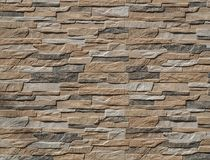 Stone wall cladding made of stripes artificial rocks. The colors are black,brown and gray . stock images