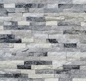 Stone wall cladding made of white and gray quartzite bricks. Background and texture stock photo