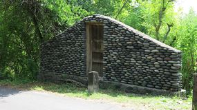 Stone wall with closed old wooden door by the road. A wall of stones in the jungle. Stones from the river that the water worked in. To smooth. Multicolored stock images