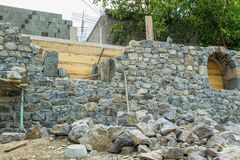 Stone wall during construction. Masonry tools on the stone wall, construction, masonry, industry Stock Photo