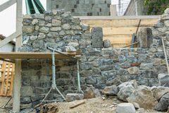 Stone wall during construction and masonry tools. Masonry tools on the stone wall, construction, masonry, industry Stock Images
