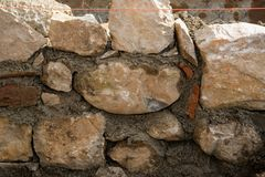 Stone wall during construction and masonry tools. Stone wall during construction, space for text Stock Photography