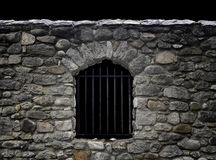 Stone wall in the dark. Stone wall with barred window in the dark Stock Photos