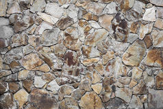 Stone wall detail of a side of a building with unique features. Rock wall with orange white and great stone put together as a facade wall used in architectural Royalty Free Stock Photography