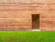 Stone wall with door and grass floor in front off Royalty Free Stock Images