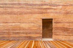 Stone wall with door and wood floor in front off Stock Photography