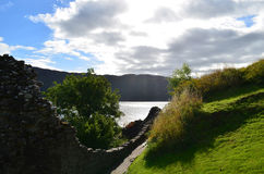 Stone Wall Encompassing the Grounds of Urquhart Castle in Scotla. Crumbling stone wall encompassing the grounds of Urquhart Castle in Scotland Royalty Free Stock Photo