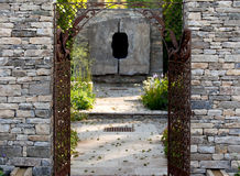Stone wall entrance to a garden. Through iron gates Royalty Free Stock Photos