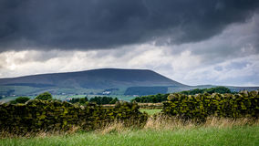 Stone wall on the farm with Pendle Hill in distance on cloudy su Stock Photos