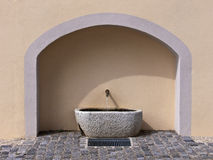 Stone wall fountain. With cobblestones in front Royalty Free Stock Photo