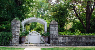 Stone Wall with Garden Gate. Old stone wall with garden gate and arbor royalty free stock photo