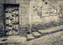Stone wall with Graffiti. Old stone wall with Graffiti in toned black and white Royalty Free Stock Images