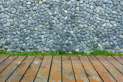 Stone wall and green grass on wood floor Royalty Free Stock Photos