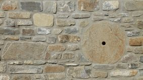 Stone wall with grinding wheel. And big stones Stock Photo