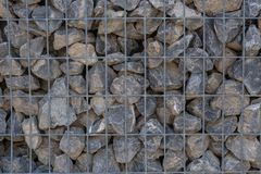Stone wall held by a metal grid. Template royalty free stock image