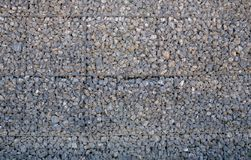 Stone wall held by a metal grid. Template stock photography