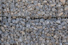 Stone wall held by a metal grid. Template royalty free stock photography