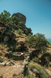 Stone wall on hilly landscape covered by rocks in Monsanto. Stone wall on hilly landscape covered by rocks and dry underbrush, in a sunny day at Monsanto royalty free stock images