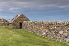 Stone wall and house at Skara Brae, Orkney, Scotland. Stock Photos