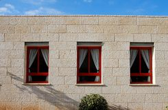 Stone wall of the house with three windows Royalty Free Stock Photography