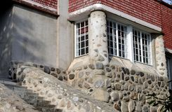 Stone wall house. Window of a house with a stone wall Stock Image