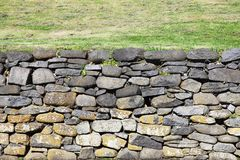 Stone wall with irregular shapes. Supporting a grassy plain Royalty Free Stock Photos