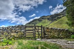 Stone wall with kissing gate. On a mountain trail near Coniston in the English Lake District royalty free stock photos