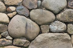 Stone wall with large and small rocks set in mortar Stock Photo