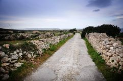 Stone wall lining a country road stock image