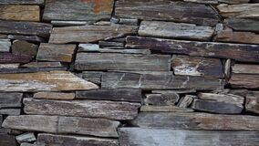 Stone wall made of multi-colored layered natural sandstone