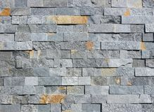 Stone wall made of natural rock bricks. Color is gray with orange spots.  royalty free stock photos