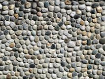 Stone wall made of oval shape pebbles of various colors. Close up, texture . Stone wall made of oval shape pebbles of various colors. Close up, texture amd stock photo