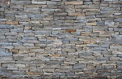 Stone wall made of rock bricks with different sizes. Colors are  shades of gray and brown. stock images