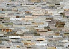 Stone wall made of striped stacked slabs of natural rocks. Cladding for exteriors,. Colors are shades of gray,pink and shades of light brown stock photography