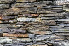 Stone wall made of various stones of different colors and shapes Stock Photo