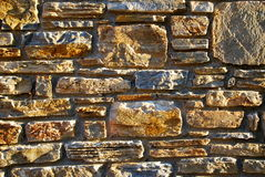 Yellow stone wall with sunshine on it Stock Photos