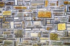 Stone wall of multi-colored stones with decorative masonry stock photos