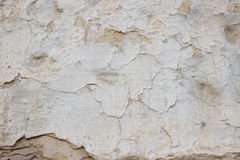 Stone wall with a multilayered old tumbling whitewash texture Royalty Free Stock Photography