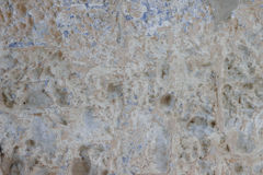 Stone wall with a multilayered old tumbling whitewash texture Stock Photos