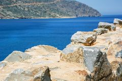 Stone wall near the sea and mountains on Crete. In Greece Royalty Free Stock Image