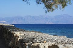 Stone wall near the sea and mountains. On Crete in Greece Stock Photography