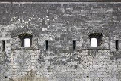 Free Stone Wall Of An Ancient Castle With Windows In The Form Of Loopholes. Close-up. Selective Focus Royalty Free Stock Images - 166415309