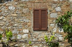Stone wall and window with closed shutters Stock Images