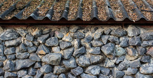Stone Wall and Old Roof Stock Photos