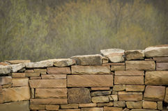 Stone Wall With Out of Focus Trees in Background Royalty Free Stock Photos
