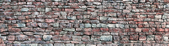 Stone wall panorama, panoramic stonewall pattern background, old aged weathered red and grey grunge limestone dolomite texture Stock Photo