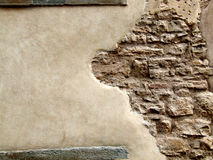 Stone wall with peeling plaster. Rough old wall made of stones - vintage Italian masonry in the Lombardy Region (Italy, Bergamo Royalty Free Stock Photo