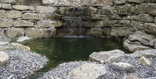 Stone wall and pond detail Royalty Free Stock Photography